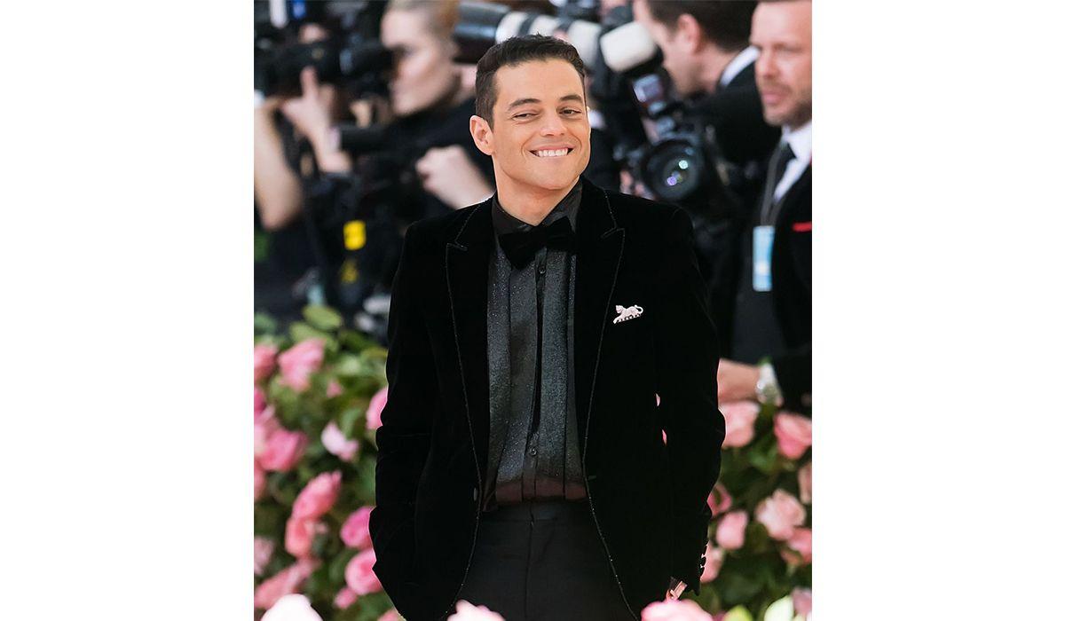 Rami Malek wearing a Panthère de Cartier brooch, and a Cartier Tank MC watch